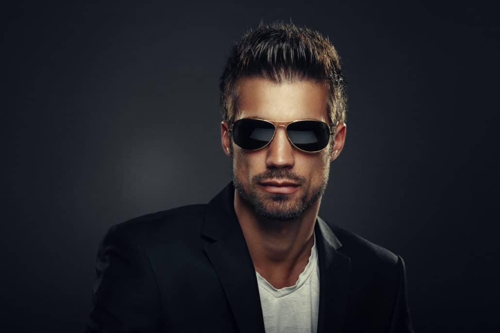 Portrait of men with sunglasses in studio on dark background